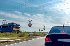 Железнодорожный переезд электропоезда причаливая Положение автомобиля перед железнодорожным переездом без барьера стоковое изображение