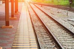 Железнодорожный путь на гравии для транспорта поезда с тоном света захода солнца Стоковое Фото