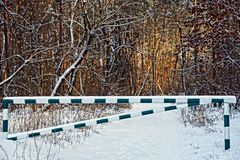 Железный барьер на дороге леса в снеге Стоковая Фотография RF