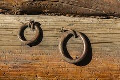 2 железных кольца пригвозженного к грубому деревянному siding Стоковое Изображение