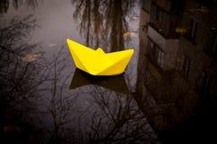 Желтая бумажная шлюпка и хмурый город осени Надежда для успеха Стоковая Фотография