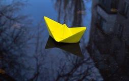 Желтая бумажная шлюпка и хмурый город осени Стоковое фото RF