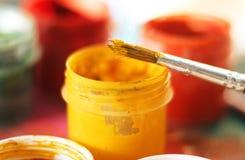 Желтая гуашь в пластиковых опарнике и кисти стоковое изображение rf