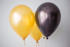 желтая и черная плавая предпосылка воздушных шаров гелия стоковая фотография rf