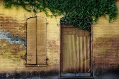 Желтая кирпичная стена с дверью и закрыванным окном стоковая фотография