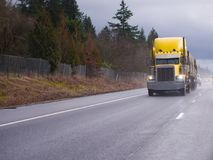 Желтая классическая большая снаряжения тележка semi бежать на идя дождь шоссе Стоковые Изображения