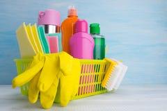 Желтая корзина с набором для очищать, на светлой предпосылке, перчатки, бутылки чистящих средств, ветошей, щеток стоковое фото rf