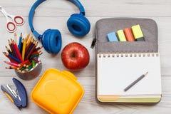 Желтая коробка сандвича, яблоко, наушники, канцелярские принадлежности и открытая тренировка Стоковые Фото