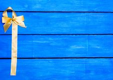Желтая лента на голубой деревянной предпосылке, смычок стоковое фото
