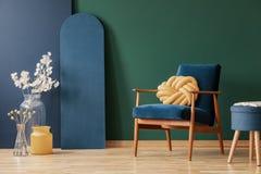 Желтая подушка на деревянном кресле в голубом и зеленом плоском интерьере с цветками и табуреткой Реальное фото стоковые фотографии rf