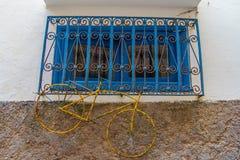 Желтая ржавая смертная казнь через повешение велосипеда на голубом окне с железной решеткой стоковые фотографии rf