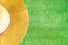 Желтая соломенная шляпа на зеленой траве имитировать предпосылки стоковое изображение rf