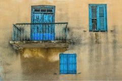 Желтая стена старого здания с темными пятнами воды лить и 3 яркими голубыми винтажными деревянными шторками на окнах Стоковое Изображение RF
