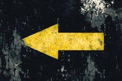 Желтая стрелка покрашенная на старом grunge и выдержанной черной предпосылке текстуры стены Стоковое фото RF