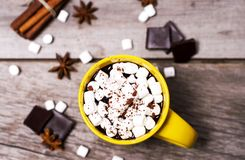 Желтая чашка какао с зефирами, анисовкой звезды и циннамоном на деревянной предпосылке стоковые фото