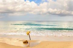 Желтая шляпа на ручке в песке около камня на пляже Стоковое Фото