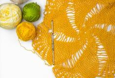 Желтое вязание крючком шнурка, шарики потока и крюк вязания крючком стоковая фотография