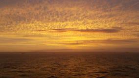 Желтое золото заволакивает на все небо во время захода солнца стоковое изображение