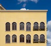 Желтое итальянское здание стиля с окнами и голубым небом Стоковые Фото