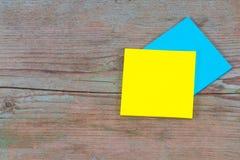 Желтое и голубое липкое примечание с пустым космосом для текста на древесине Стоковые Изображения RF