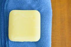 Желтое мыло и голубое полотенце на деревянном столе Стоковые Изображения RF