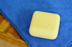 желтое мыло и голубое полотенце на таблице Стоковое Фото