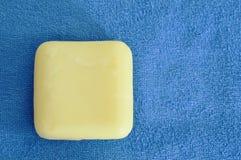 Желтое мыло и голубое полотенце Стоковое Изображение