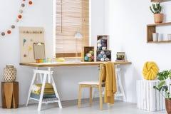 Желтое одеяло на стуле на деревянном столе с лампой и красочными пряжами в современном интерьере Реальное фото стоковые изображения