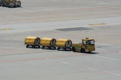 Желтые вагонетки перевозки с нагруженным багажем на гудронированном шоссе взлётно-посадочная дорожка стоковые изображения