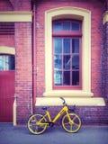 Желтые велосипед и кирпичное здание стоковые изображения