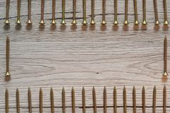 Желтые винты в 2 строках на деревянной предпосылке стоковая фотография