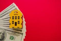 Желтые деревянные модельные дом и доллары на красной предпосылке с космосом экземпляра стоковые фото
