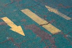 Желтые знаки стрелки на голубом асфальте Стоковые Изображения RF