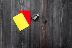 Желтые и красные карточки и свисток рефери на деревянном copyspace взгляд сверху предпосылки Стоковые Изображения