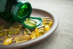 Желтые капсулы и зеленый цвет желатина cholecalciferol витамина D3 Стоковые Фото
