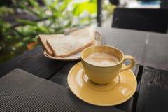 Желтые керамические чашка кофе и хлеб на деревянном столе Стоковые Изображения