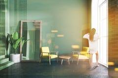 Желтые кресла зеленеют живущую комнату, зеркало, женщину Стоковое Фото