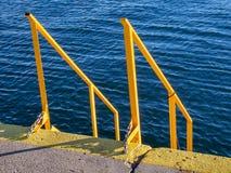 Желтые лестницы и поручни на доках - темносинее море на заднем плане стоковое фото rf