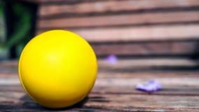 Желтые пластичный шарик на коричневой деревянной выносливости и сильные ослабляют жизнь стоковое изображение