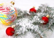 Желтые рождества красивые и красные шарики с ветвью и снегом ели на белой предпосылке Стоковая Фотография