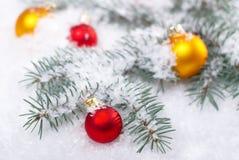 Желтые рождества красивые и красные шарики с ветвью и снегом ели на белой предпосылке Стоковые Изображения