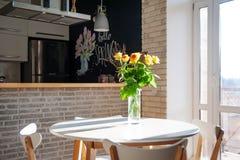 Желтые розы в стеклянной вазе на таблице Праздники и концепция торжества стоковая фотография rf