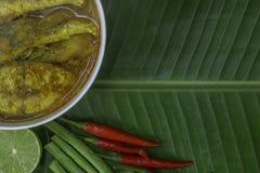 Желтые рыбы луциана карри с стержнями лотоса, южной тайской пряной едой и свежим овощем в белом блюде на банане листают/селективн Стоковое Изображение RF