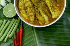 Желтые рыбы луциана карри с стержнями лотоса, южной тайской пряной едой и свежим овощем в белом блюде на банане листают/селективн Стоковое Фото