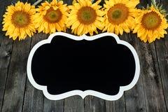 Желтые солнцецветы и черный модель-макет на деревянной предпосылке для творческого дизайна стоковое фото rf