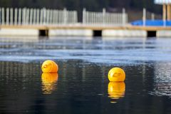 Желтые томбуи против открытого моря Ограничение на открытой воде стоковые фото