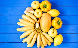 Желтые фрукты и овощи изолированные на голубой предпосылке Стоковое фото RF