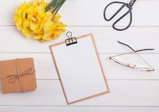Желтые цветки и доска сзажимом для бумаги весны с чистым листом бумаги на белом деревянном столе стоковое фото