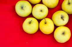 Желтые яблоки на красном цвете Стоковые Изображения RF