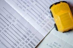 Желтый автомобиль игрушки помещенный на банковской книжке на предъявителя банка на взгляд сверху Стоковое Фото